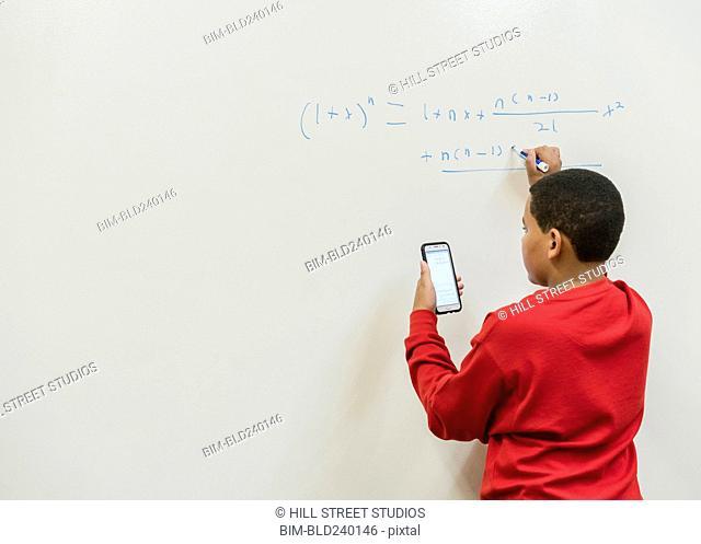 Teenage boy holding cell phone writing equation on whiteboard