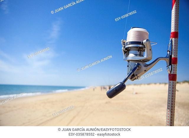 Fishing reel on rod detail with angling fishers at bottom on the sea, Huelva, Spain