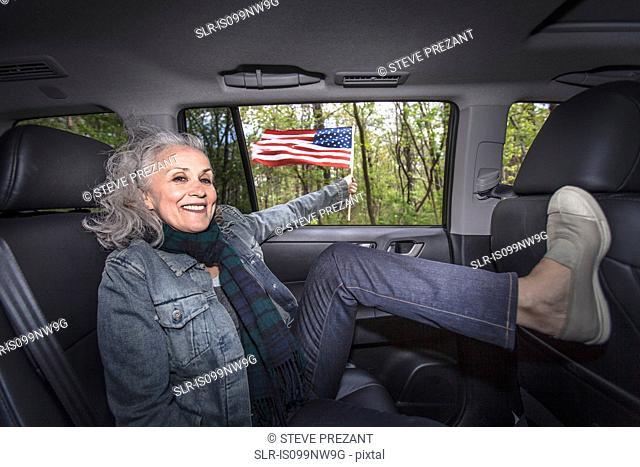 Senior woman relaxing in backseat of car, portrait