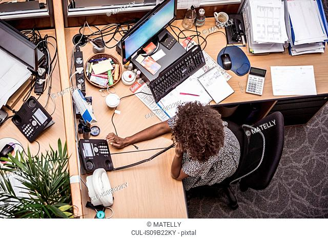 Overhead view of businesswoman talking on landline at office desk
