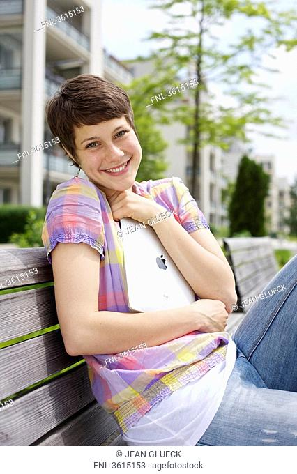 Young woman embracing iPad on a bench