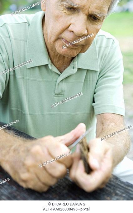 Senior man whittling piece of bark, close-up