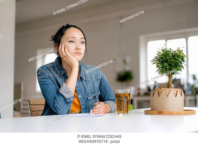 Thoughtful young woman sitting at table with plant and glass of tea