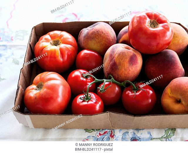 Box of fresh tomatoes and peaches