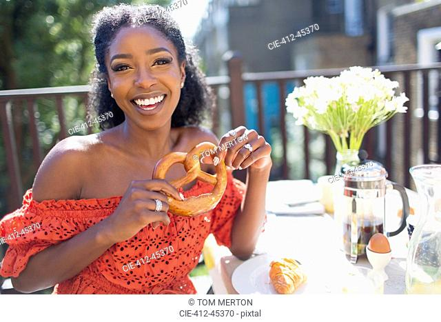 Portrait smiling, confident young woman with pretzel enjoying breakfast on sunny balcony
