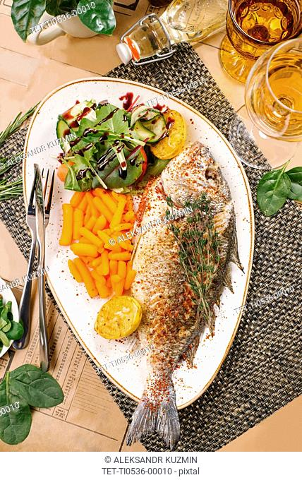 Fried fish with baby carrots and salad