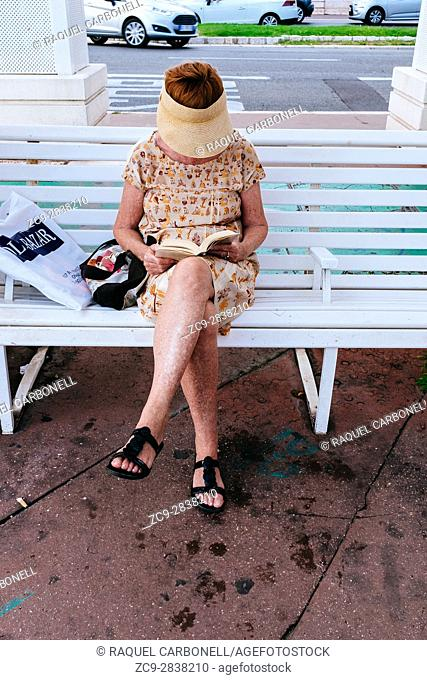 Mature woman sitting on a bench reading a book in Promenade des Anglais. Nice, Alpes-Maritimes, French Riviera, Provence-Alpes-Côte d'Azur, France