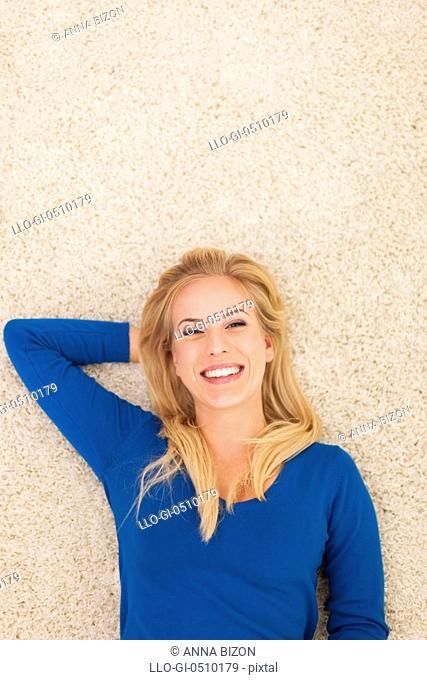Beautiful smiling woman lying down on carpet Debica, Poland