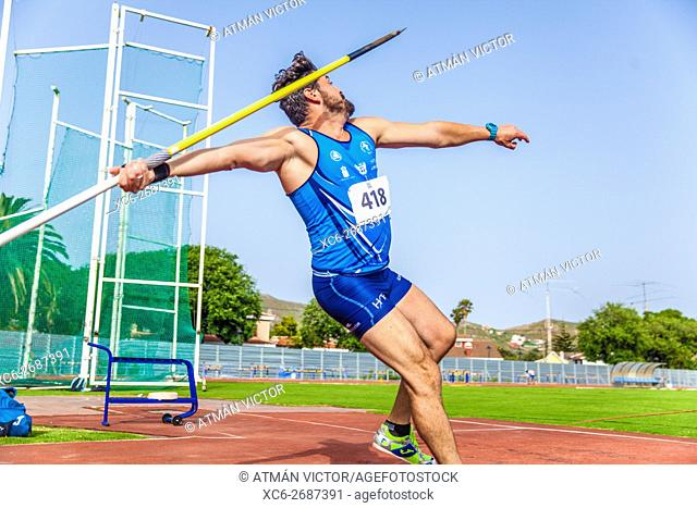 Young sportsman throwing javelin on an athletic piste