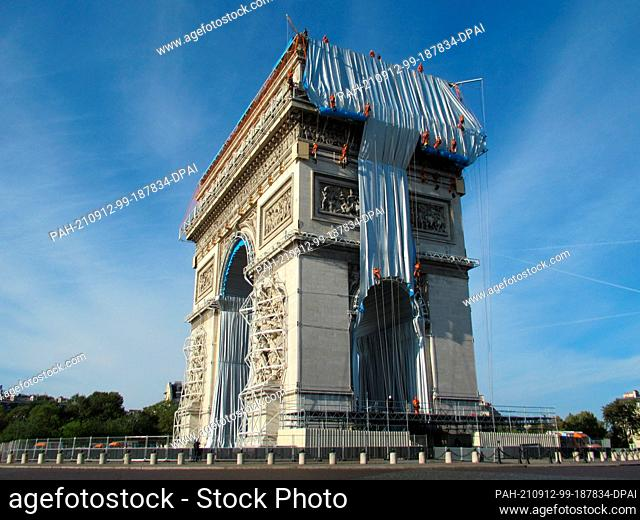 dpatop - 11 November 2021, France, Paris: Climbers have begun wrapping the Arc de Triomphe. The wrapping is to be completed by September 18