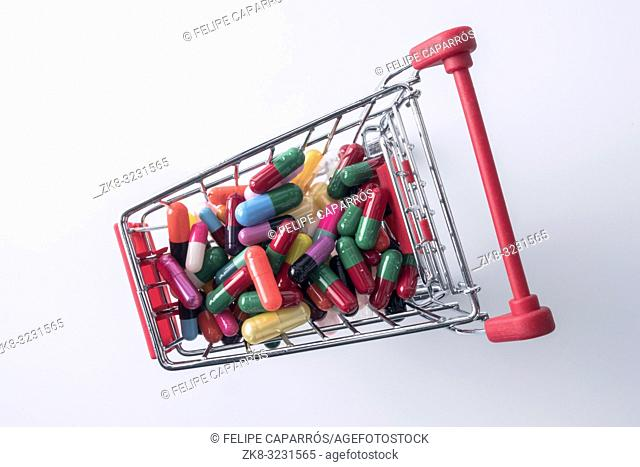 Shopping cart with capsules isolated on white background, composition horizontal