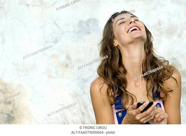 Young woman holding cell phone, laughing