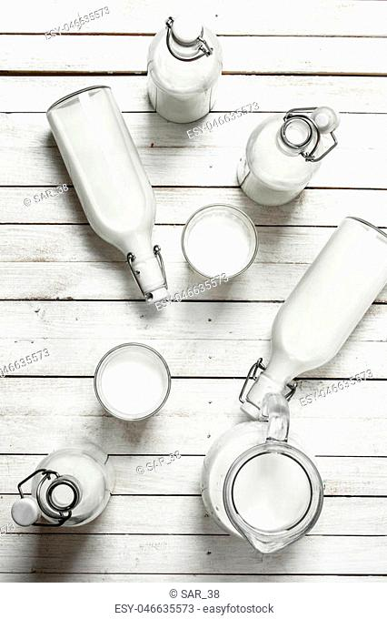 Fresh milk in bottles . On a white wooden table