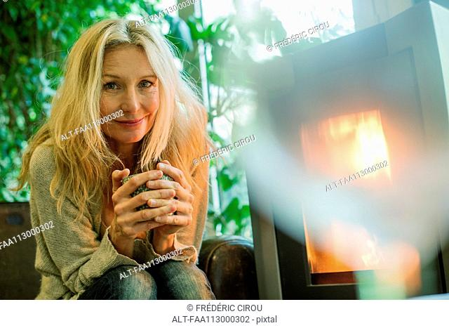 Mature woman relaxing by fireplace with warm drink, portrait