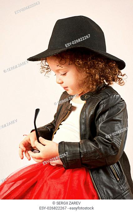 Little girl with black hat sitting looking over sunglasses