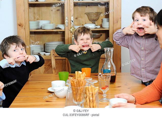 Boys making faces at table