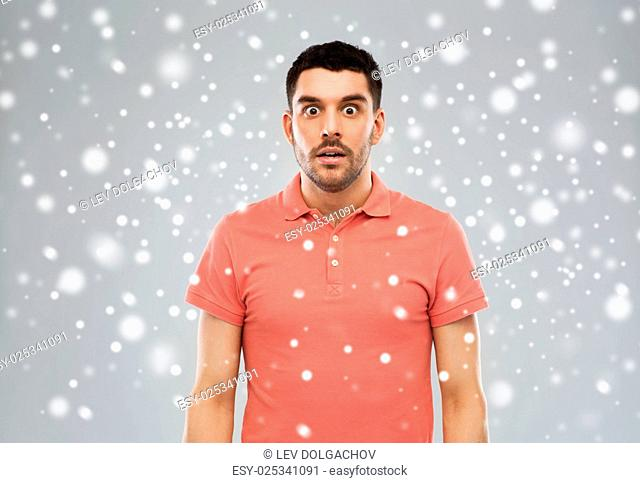 emotion, winter, christmas and people concept - surprised man in polo t-shirt over snow on gray background