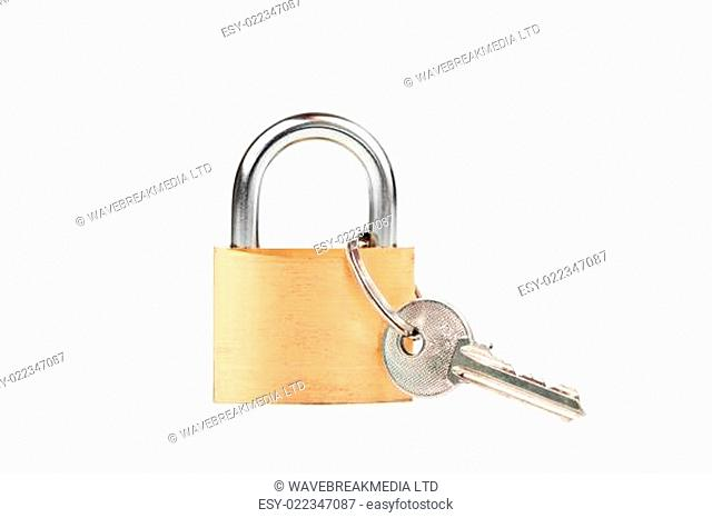 Padlock standing with key hanging against white background