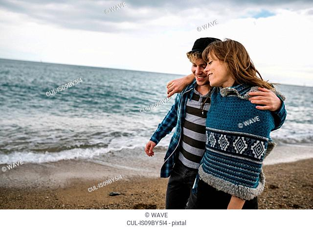 Romantic young couple strolling on beach, Barcelona, Spain