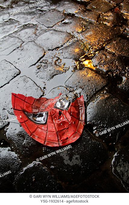broken spiderman plastic mask on wet road in city town