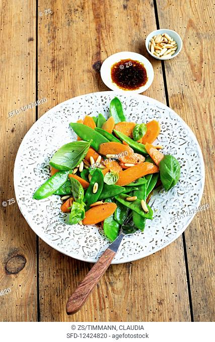 Mange tout salad with carrots and pine nuts