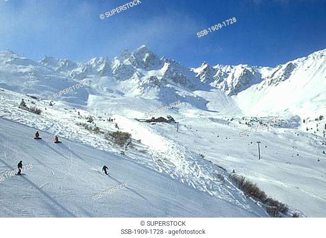 Courchevel ski slopes in mountains of the Trois Vallees Three Valleys ski region of French Alps France Europe Skiers enjoy sun sunshine on snowy slopes with...