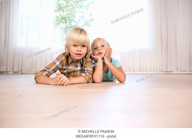 Brother and sister lying on the floor at home grimacing