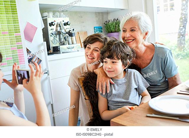 Young girl photographing, brother, mother and grandmother, using smartphone