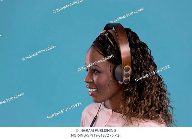 Happy African Woman listening to music on headphones. Young fresh African female model on blue background