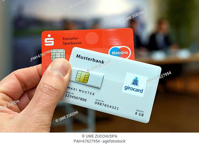 A hand holds up examples of the 'Girocard City' and an ec card at a press conference in Kassel, Germany, 20 April 2016. Contactless paying and other innovations...