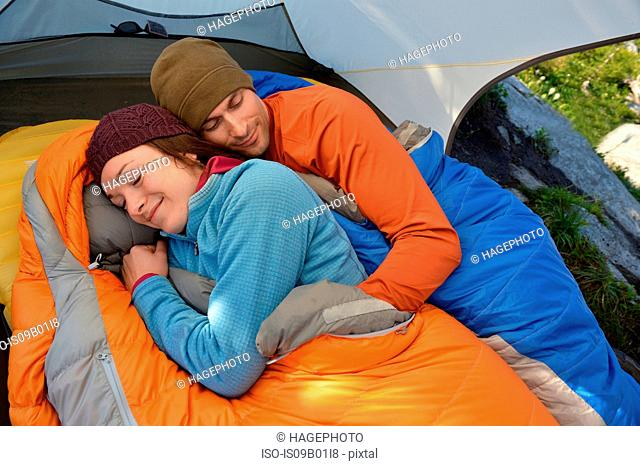 Couple hugging in sleeping bags in tent at Fault Lake, Selkirk Mountains, Idaho