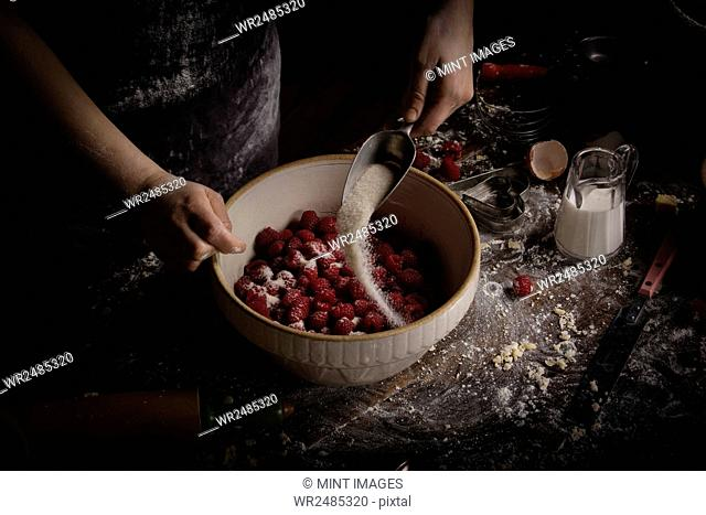 Valentine's Day baking, woman preparing fresh raspberries in a bowl, adding sugar