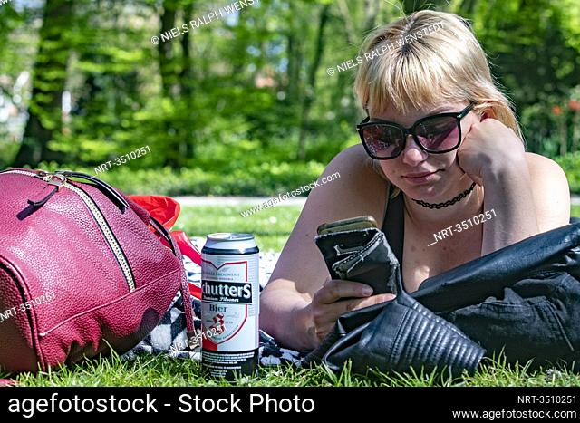 DORDRECHT- An young woman enjoys the sun in a park during the Coronavirus