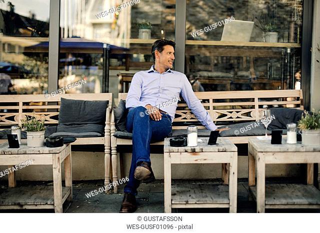 Businessman sitting in coffee shop, smiling