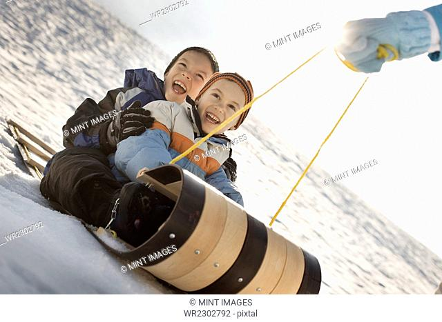 A person pulling two children along on a sledge