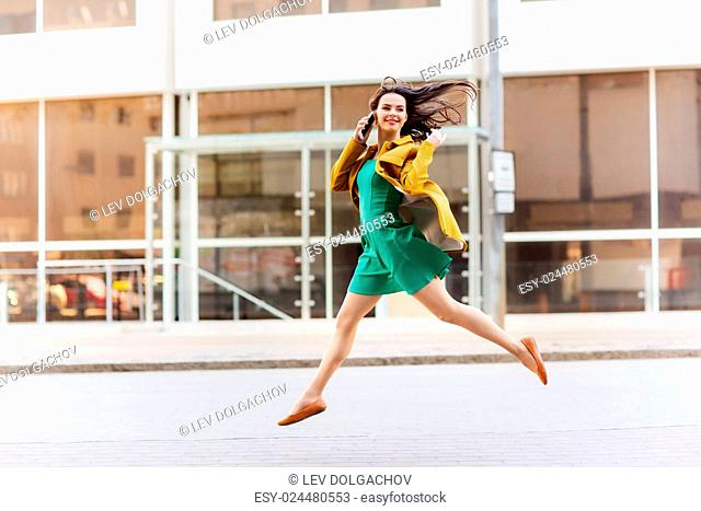technology, communication and people concept - smiling young woman or girl calling on smartphone on city street and jumping high