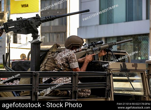14 October 2021, Lebanon, Beirut: A Lebanese soldier takes aiming position in the area of clashes where gunfire erupted at a protest by supporters of the Shiite...