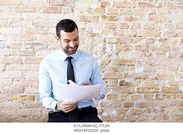 Smiling businessman reading document at brick wall