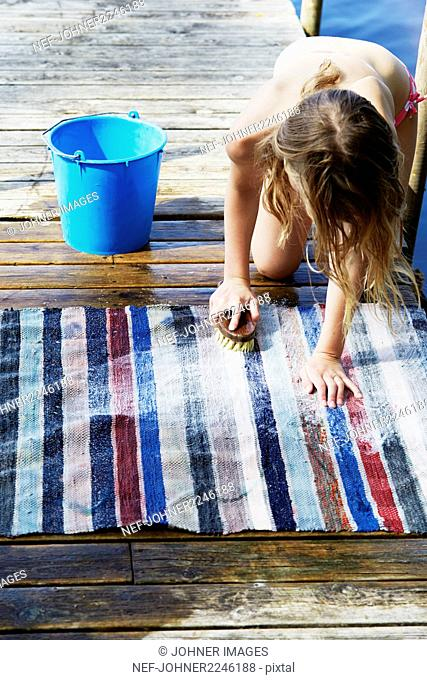 Girl cleaning rug