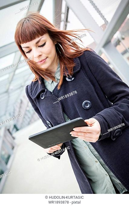 Young woman in airport building using digital tablet