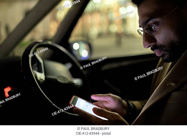 Man using smart phone in car at night