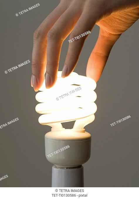 Woman screwing in energy-efficient light bulb