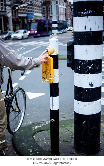 Old Biker Pushing button for traffic light in Amsterdam, The Nederlands