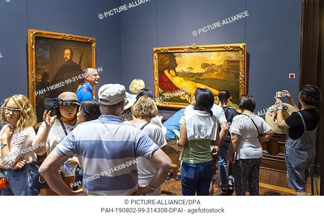 """02 August 2019, Saxony, Dresden: Numerous visitors are looking at the work """"""""Slumbering Venus"""""""" (r) by Titian/Giorgione in the exhibition """"""""Highlights of the..."""