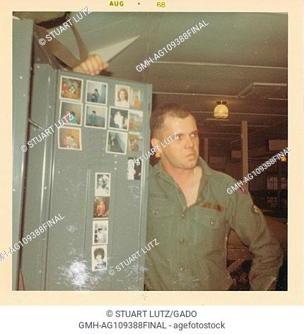 A United States soldier holds open the door to his locker to display his collection of personal photographs, Vietnam, 1968