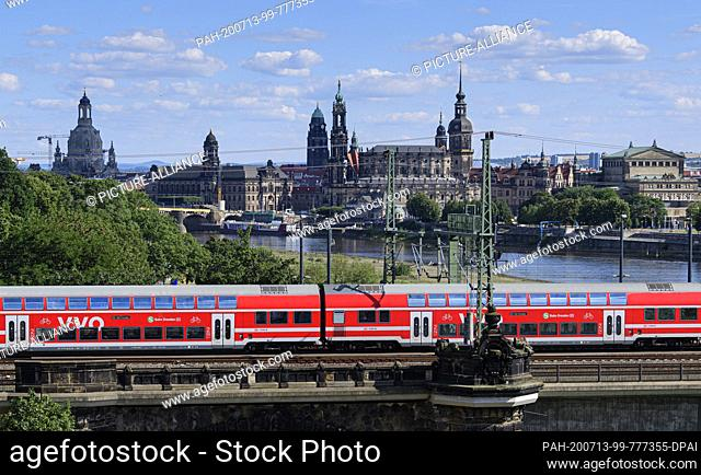 13 July 2020, Saxony, Dresden: A suburban train runs in front of the historic old town scenery with the Frauenkirche (l-r), the Ständehaus, the Hofkirche