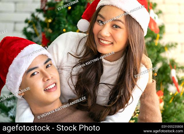 Young asian adult teenager couple hugging and celebrateing christmas holiday together in living room with christmas tree ornament decoration