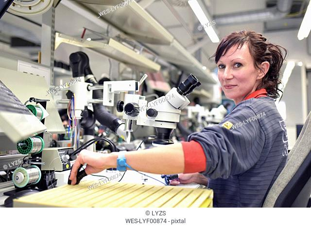 Woman working on quality control in the manufacturing of circuit boards for the electronics industry