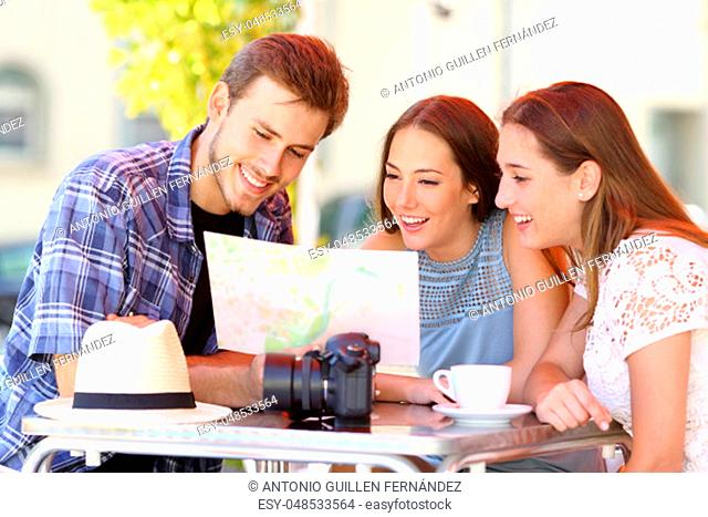 Three happy tourists planning travel consulting a paper guide in a bar terrace