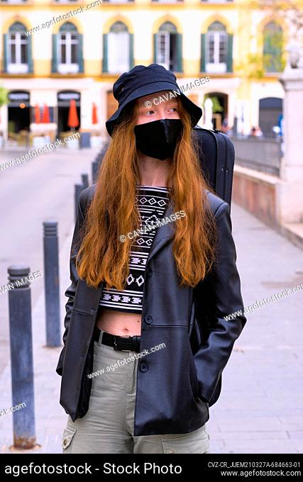 Young red-haired woman with antivirus mask on the city streets w